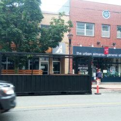 La terrasse noire fabriquée à partir d'un conteneur. Elle est placée devant le restaurant. Entre les deux, il y a un grand arbre.