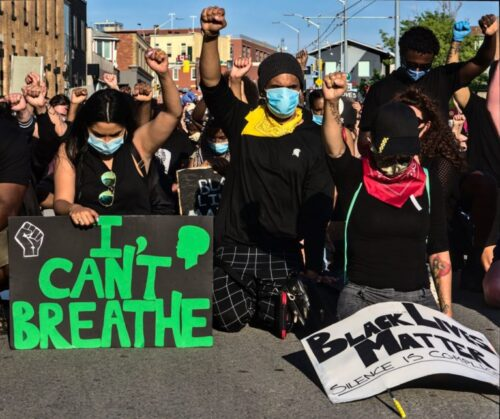 "A close up of the front line of a huge crowd of people with their fists-raised are kneeling in the street in Kitchener during the Black Lives Matter protest. In the foreground signs reading ""I can't breath"" and Black Lives Matter."