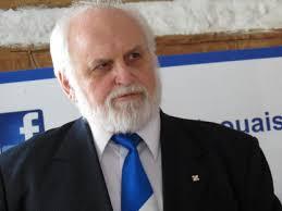 Jean-Paul Perreault vêtu d'un complet avec une cravate bleue