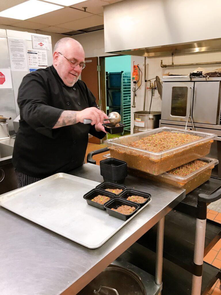 Le chef Pat Mills assemble des plats dans sa cuisine