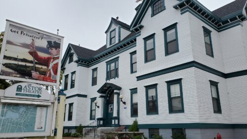 A photo of the outside of the white Astor Theatre building in Liverpool, Nova Scotia on an overcast day