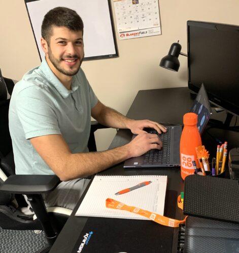 Derick Bourgeois assis à son bureau devant un ordinateur portable et une bouteille d'eau orange du CCNB