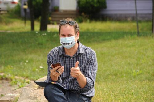 Jean-Pierre Caissie le pouce en l'air et portant un masque