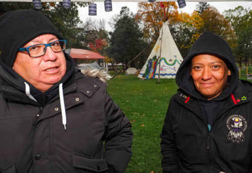 A photo of Shawn Johnston and Amy Smoke wearing toques with the White tee-pee of O:se Kenhionhata:tie/Land back Camp in the background.