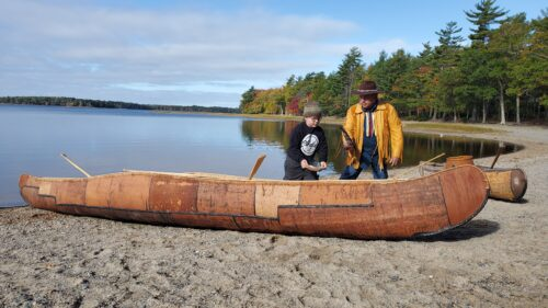 Todd Labrador and his grandson Tepkunaset smudge the canoe before launch.