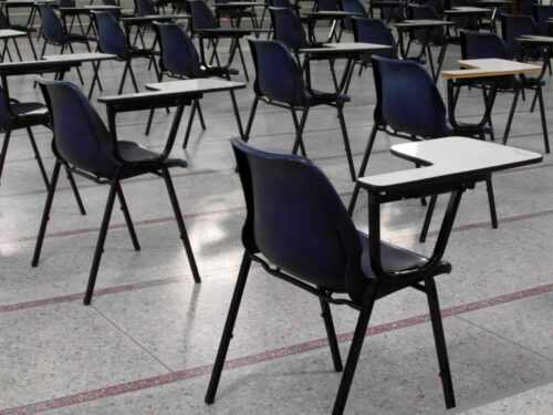 Empty desks are shown in a classroom.