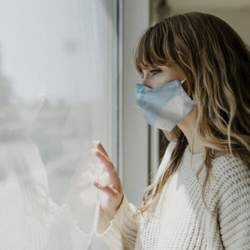 A woman with a medical face mask looks out the window. Photo by: Pxhere