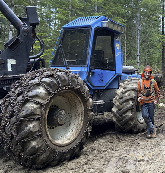 Nick Gagnon stands next to a large vehicle.