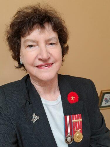 Élizabeth Allard vêtu d'un veston noir sur lequel est accroché un coquelicot et deux médailles