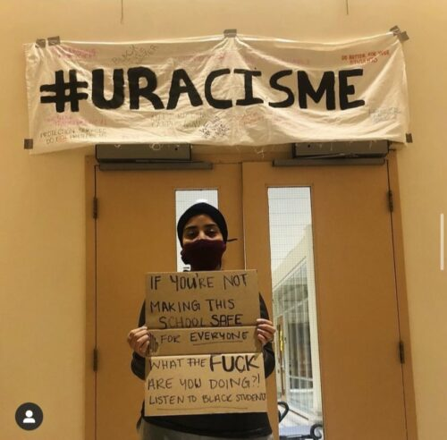Student holding up a banner during protest with #Uracisme banner in Main Hall of Tabaret Building. Photo courtesy of the @khadijax23 Instagram page.