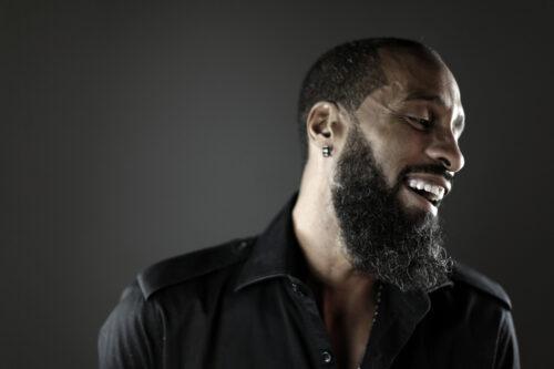 Marco Volcy souriant et portant une chemise noire sur fond gris-noir, portant barbe et moustache
