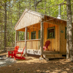 A wooden Kejimkujik camping lodge in the woods with red chairs on the deck