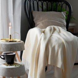 Une chaise sur laquelle jonche une couverture est placée à côté d'une chandelle et une tasse de café.