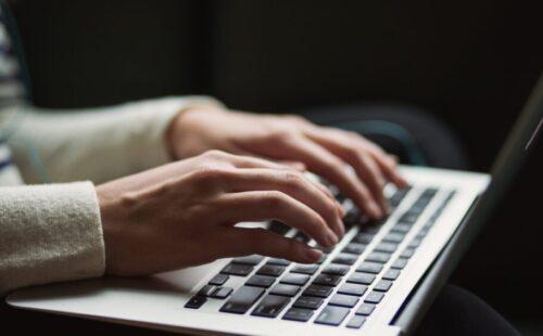 Les mains d'une femme tape sur un clavier d'ordinateur macbook de Apple.