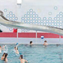Enfants qui jouent dans une piscine intérieure, avec une glissoire en arrière plan