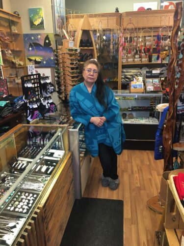 Store owner stands beside her display case, looking concerned.