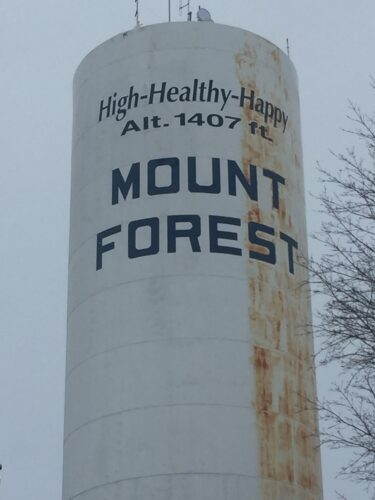 The Mount Forest water tower shows the old town slogan 'High-Healthy-Happy.'