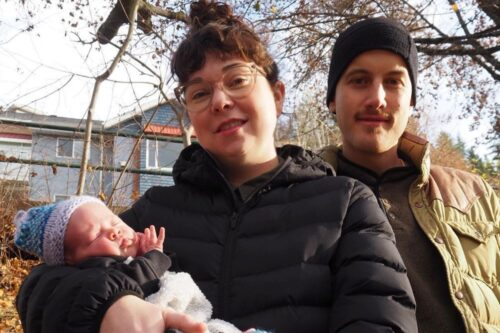 A man and woman hold a newborn baby