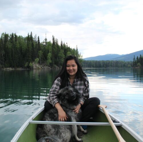 An image of Dara Campbell and her dog in a canoe on a lake, trees and blue sky in the background.