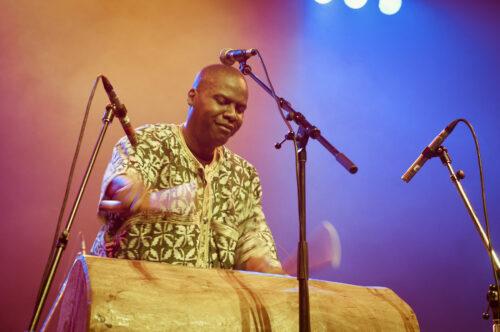 Zekhul sur scène jouant le Nkuu sur fond scénique
