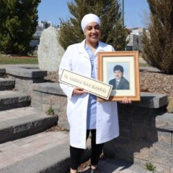 Dr. Kandola stands in front of stone steps with a photo of her father