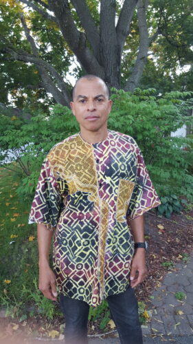 A photo of Robin Browne standing in a patterned T-shirt