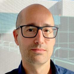 Homme avec lunettes noires habit de chandail bleu foncé debout devant une vitrine.