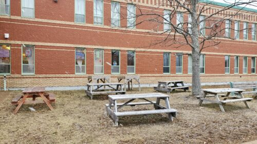 The outside of the red brick Liverpool Regional High School building is shown with a courtyard with five wooden picnic tables outside