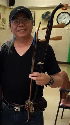 photo of Peter Bok holding is erhu instrument and smiling