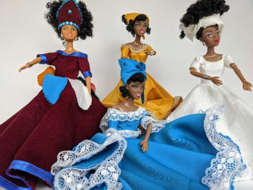 Four Black dolls with curly hair and colourful gowns