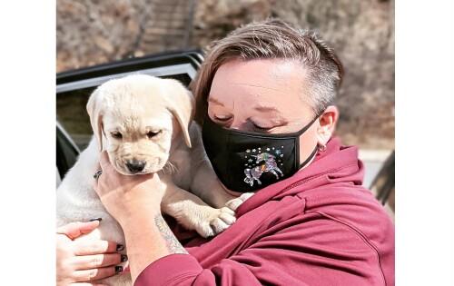 Bev Wells tenant un petit Labrador de 10 mois dans ses mains. Elle porte un masque noir avec une licorne dessus.