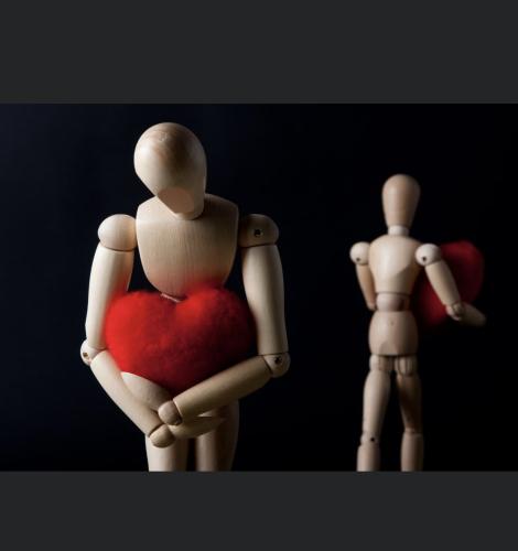 Deux bonhommes en bois se fait dos a dos en tenant un coeur en peluche. (Photo: page Facebook du Laboratoire de recherche sur le couple.)