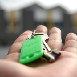 Une clé dans une main devant des maison