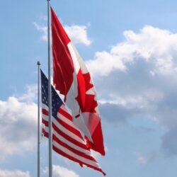 Un drapeau du Canada et un drapeau des États-Unis photographié dans un ciel bleu et quelques nuages.