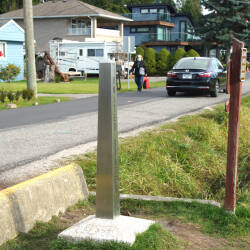 A single car driving along a road, beside the ditch that marks the Us Canadian border