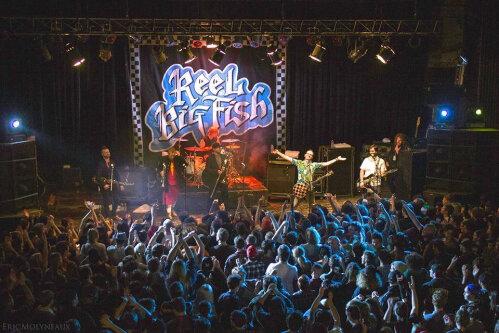 Un groupe de musique sur scène avec une foule.