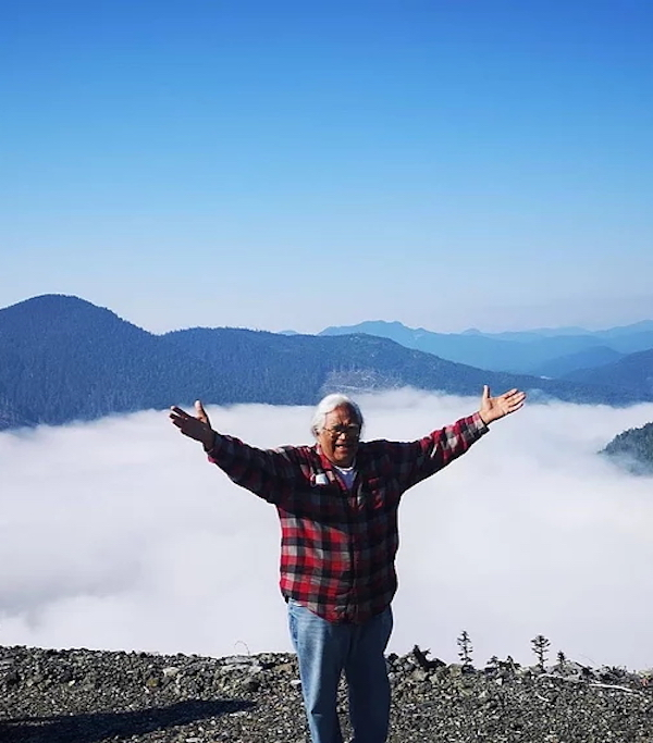 A indian elder. standing on a hilltop, lifts his hands to the sky