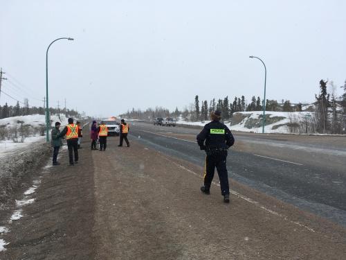 Un policier marche sur la route, se dirige vers des agents postés à un barrage routier.