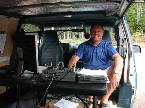 A person sits in the back of a van with a microphone and other equipment.