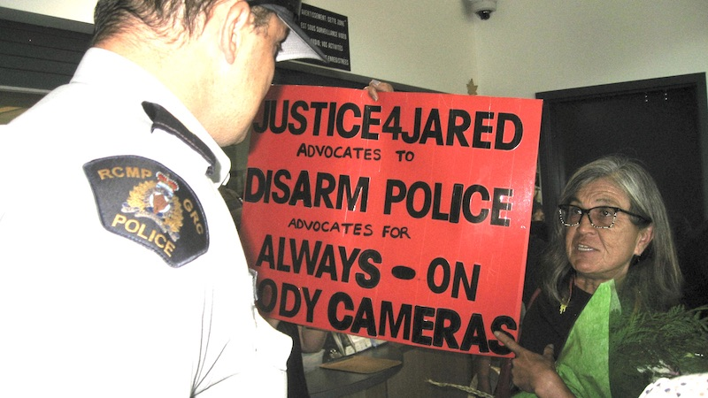 A woman with a red protest sign confronts RCMP officer inside a station