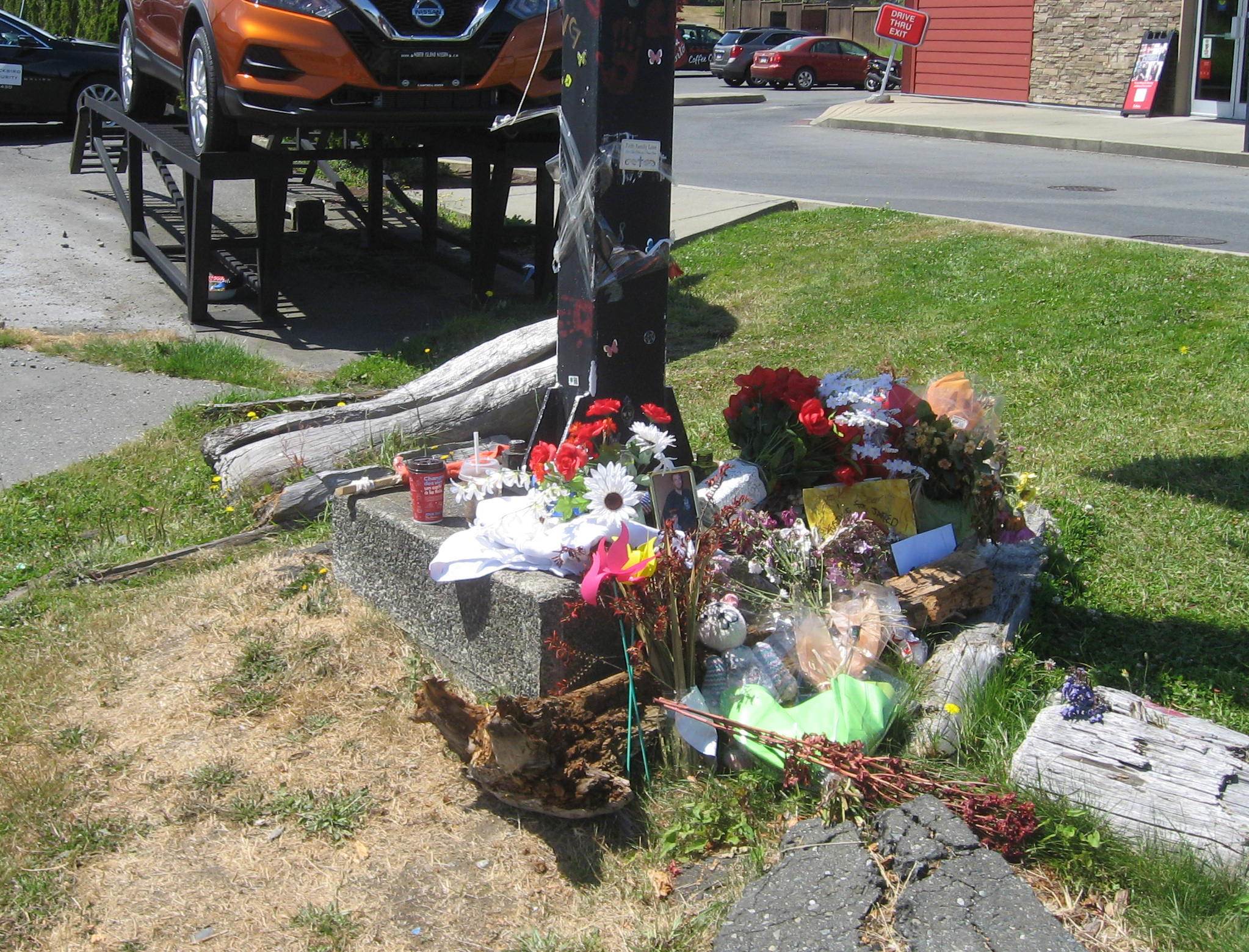 Flowers, posters, notes and photographs placed around a streetlamp across from where Jared Lowndes was killed
