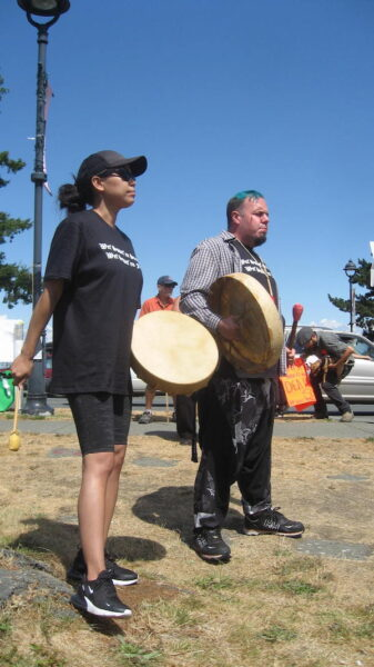 A man and a woman with drums in downtown Campbell River on a sunny day