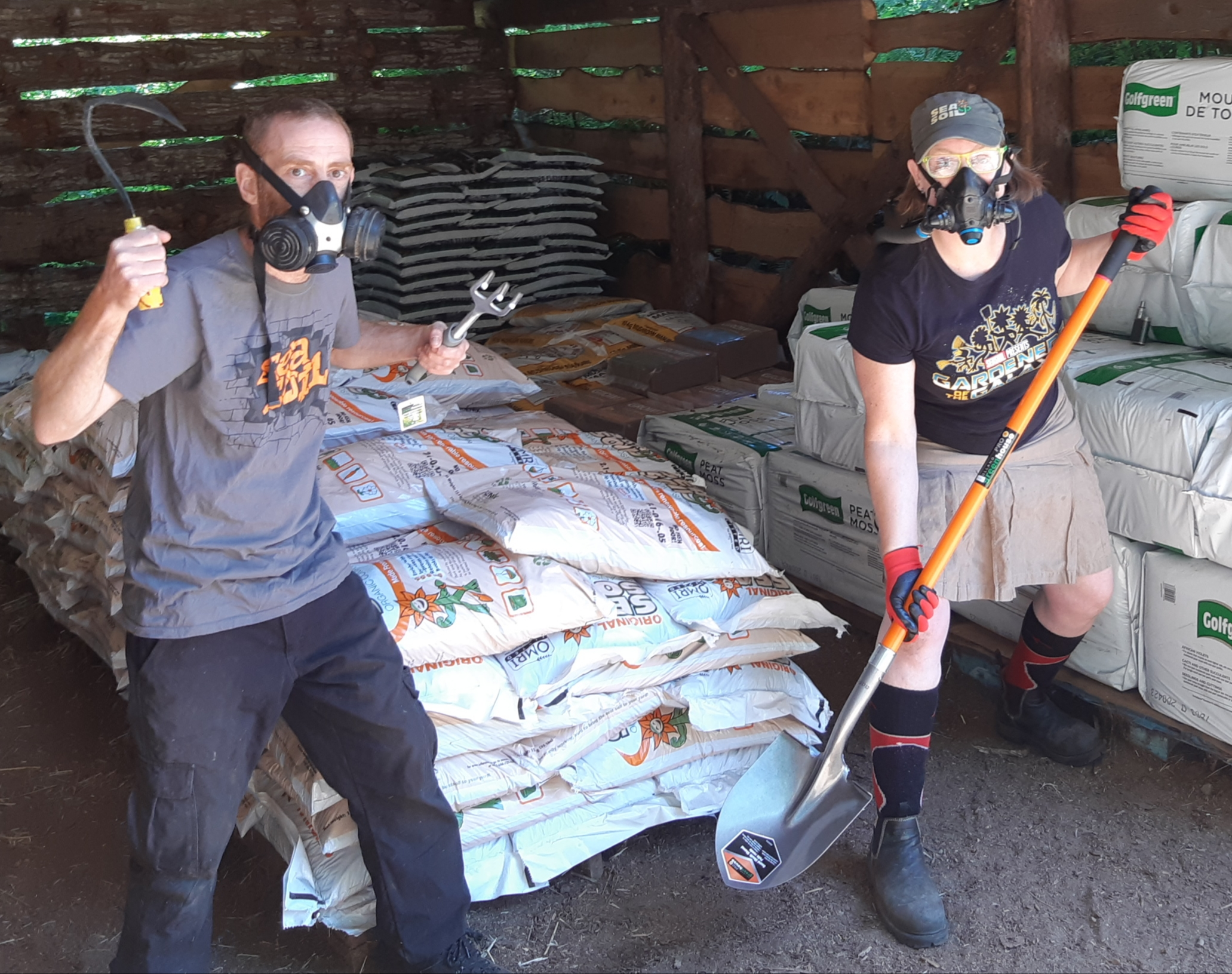 A man and a woman with gardening tools stand in a wooded room with other farm goods and bags of fertilizer behind them.