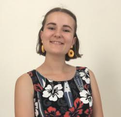 Violette, une jeune femme d'une vingtaine d'année avec une robe à fleur devant un fond unis couleur blanc cassé