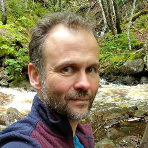 Philippe Lagacé-Wiens dehors dans une forêt en égo-portrait, porte une veste bleue et mauve.