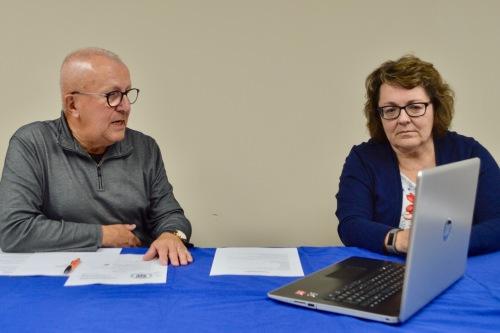 Homme avec chandail gris et femme avec chandail bleu assis à une table regardant écran de portable.