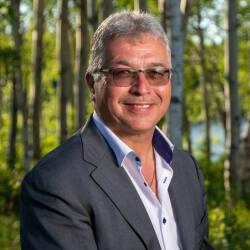 Vêtu d'un veston et d'une chemise décontractée, le cadidat pose devant une forêt de bouleaux