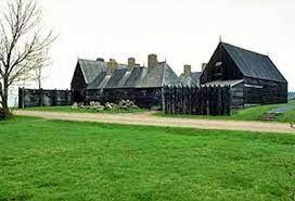 Ensemble de bâtiments en bois groupés autour d'une cour centrale.