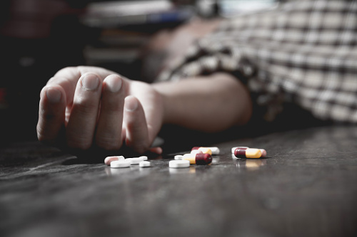 Une main blanche étalée sur le sol entourée d'une boîte de pilule sur le sol.
