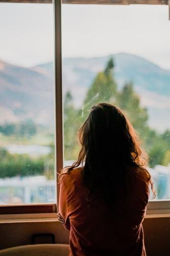 Jeune femme avec cheveux longs et manteau brun regardant à l'extérieur par la fenêtre d'une maison.